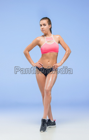 muscular young woman athlete posing at